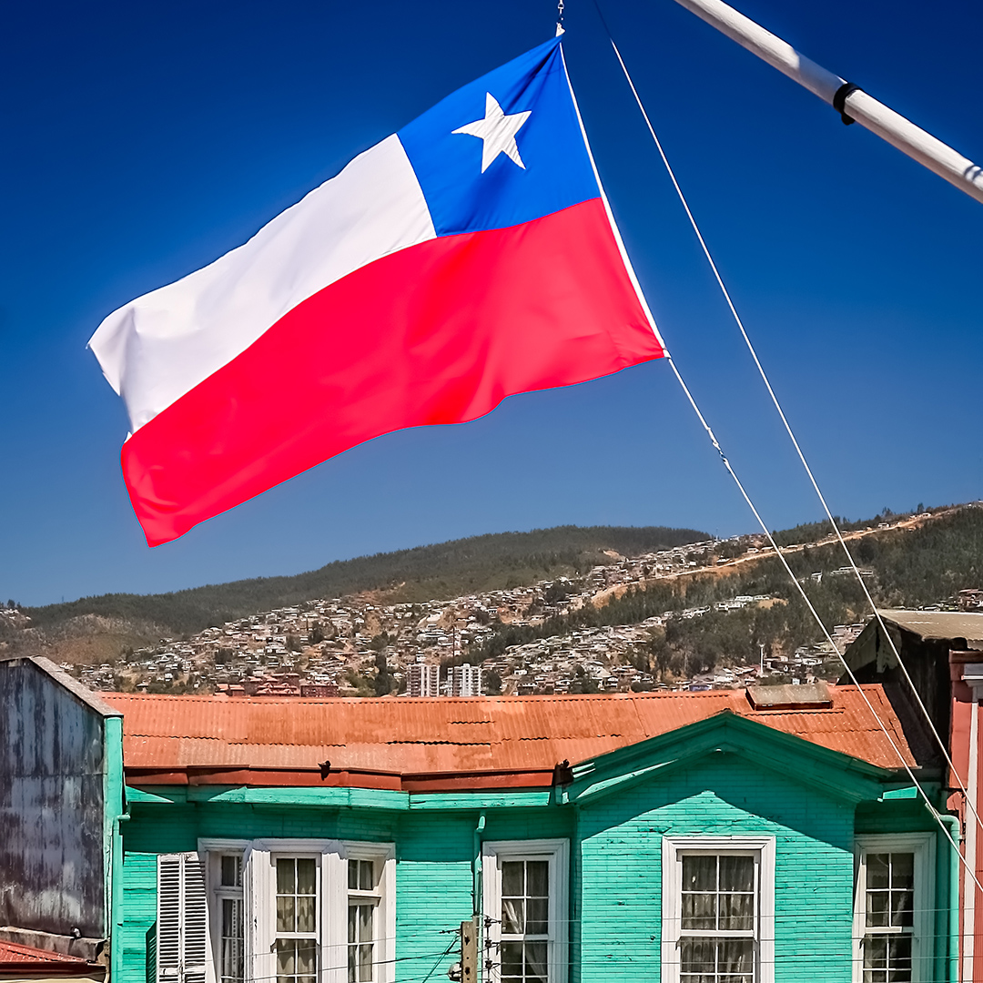 Red, white and blue chilean flag fluttering on a mast in front of the traditional old wooden building on the hilly street in Valparaiso, Chile, South America